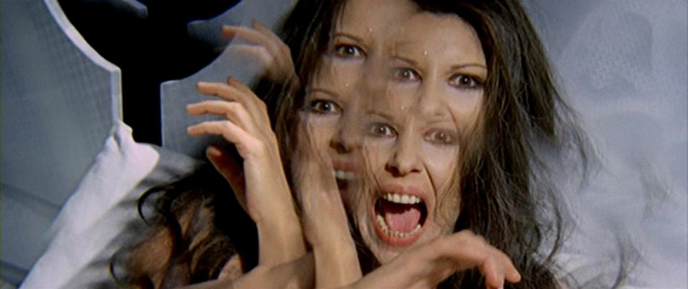 All The Colours of the Dark 1972 giallo horror movie. Woman stares at the camera and screams. The image is distorted and shows her twice with it blurring and overlapping.