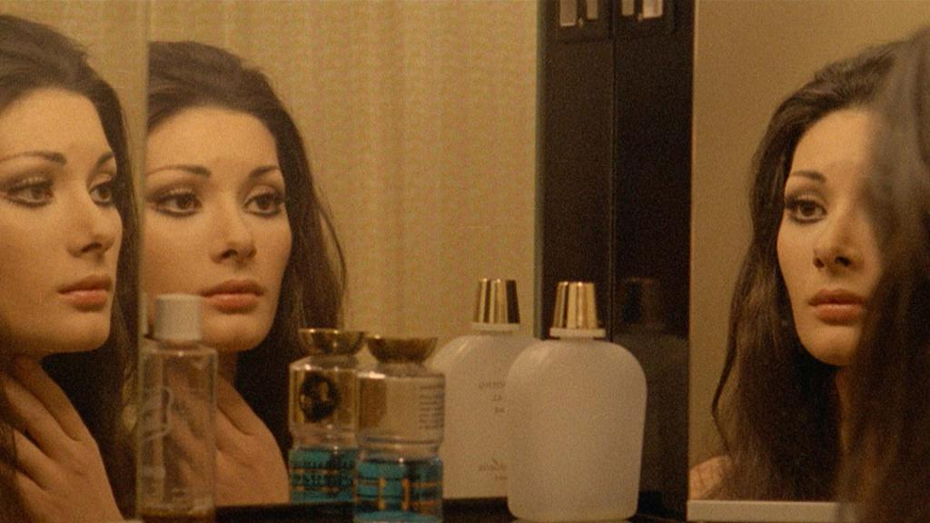 A woman sorrowfully stares at herself in the mirror. The angle of the image causes the woman to be reflected three times. She has perfume bottles in front of her. All The Colours of Dark 1972 giallo movie picture.