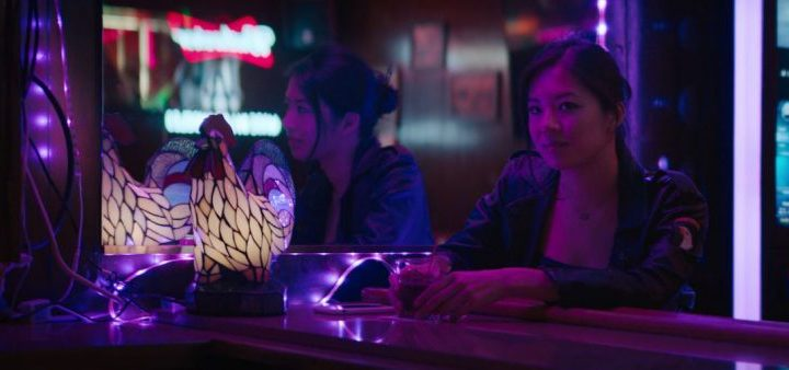 A young woman sites at a bar lit in neon purple lights and looks intrigued at something off camera. Still from horror film Blinders from FrightFest 2020