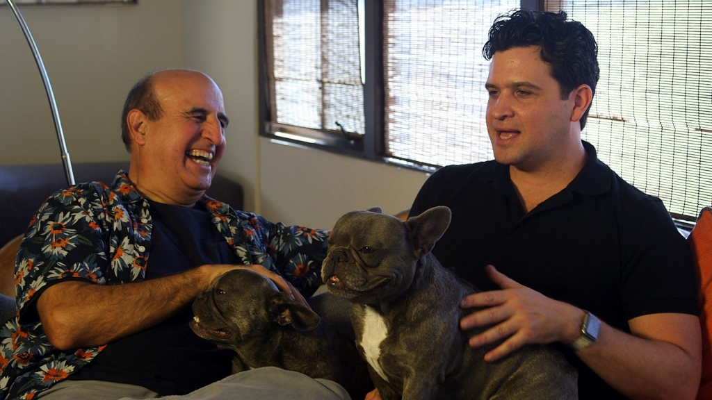Two men sat on a sofa together. One is laughing and the other is mid sentence. They are both holding French bulldog dogs.