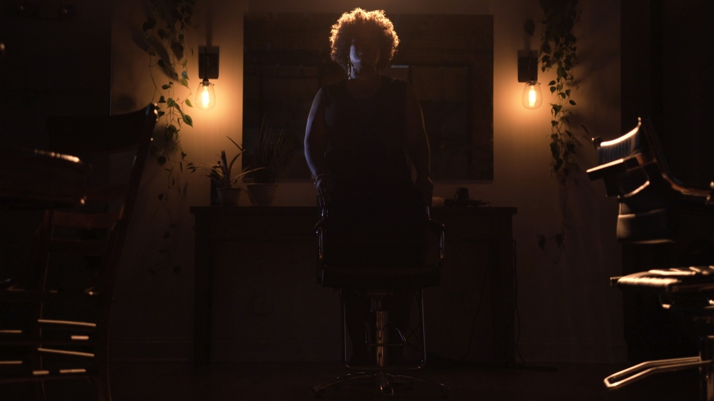 Very dark image lit by two small lights in the background to reveal a woman's silhouette and two chairs next to her. Still from short horror film called Terror Time.