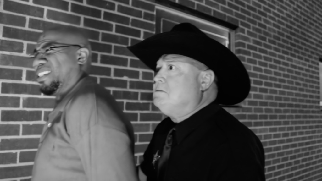 Black and white image of two men walking past a brick wall. One is a black man with glasses and he is grimacing. The other is a white man with a black cowboy hat on looking angry. Still from short horror film The Black Dude Lives!