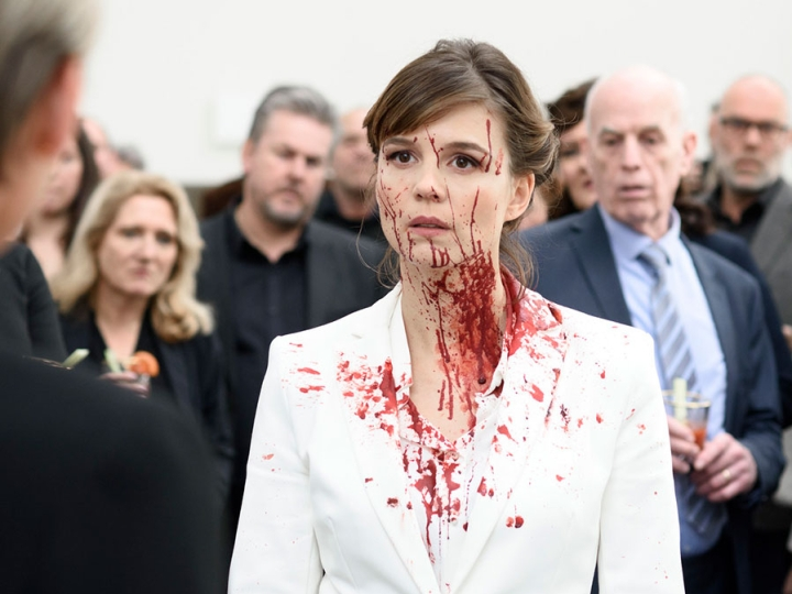 A woman is stood in the middle of a crowd of people all wearing suits and staring at her. She is wearinf a white suit and is splattered in blood, on her face, neck and chest. She looks perplexed. Still from The Columnist horror film from FrightFest 2020.